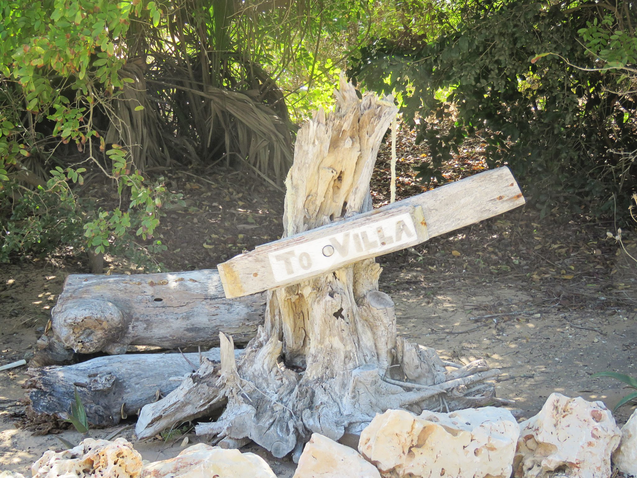 driftwood sign pointing to the villa at santorini mozambique