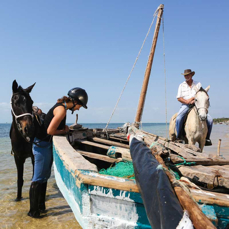 lady looking in a dhow whilst on horse safari in vilanculos mozambique