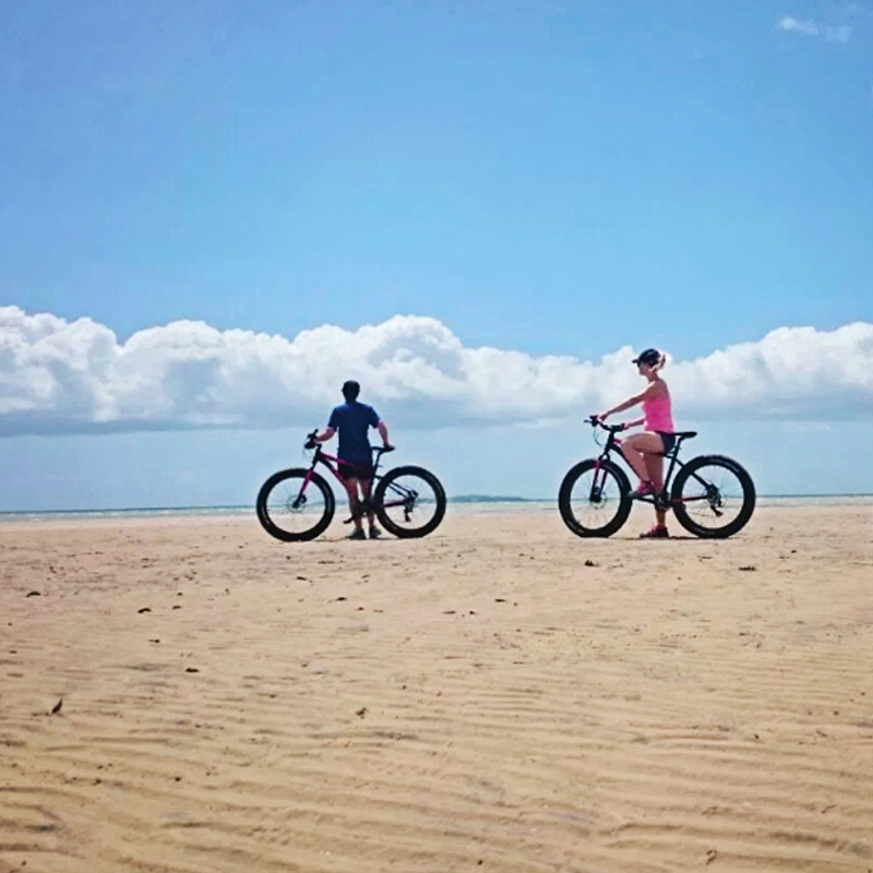 guests exploring the beach on fat tyre bicycles